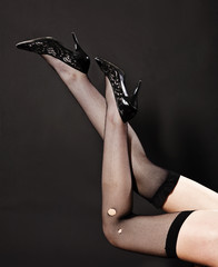 Seductive woman's legs with stockings and lacquered shoes on