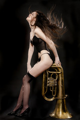 Passionate brunette sits on  saxophone
