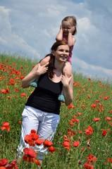 Family walking in poppy field