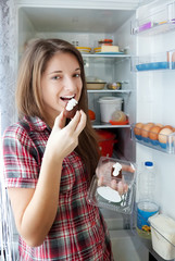 girl eating  pastry from  fridge