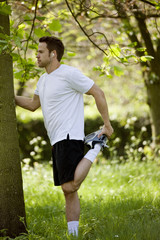 A young man stretching before running in the park