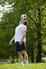 A young man balancing a football on his forehead