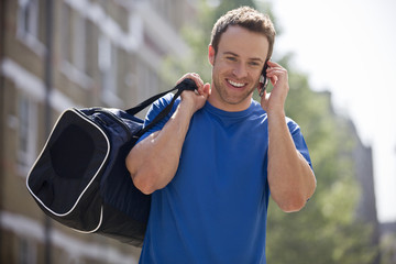 A young man carrying a sports bag, talking on a mobile phone