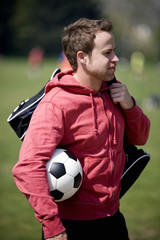A young man carrying a football and a sports bag