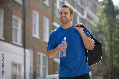 A young man in the street, carrying a sports bag