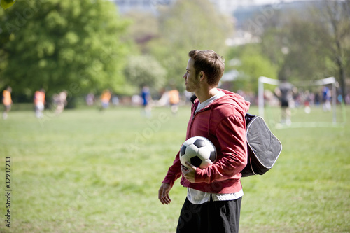 A young man standing in the park, carrying a football