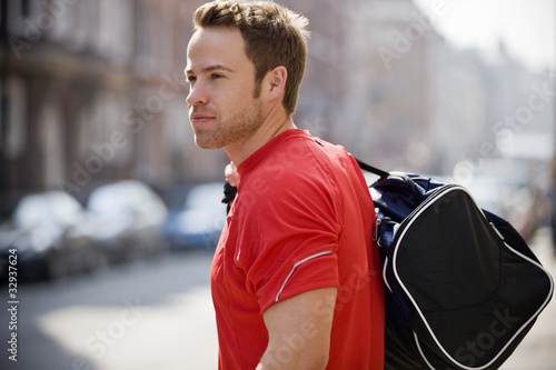 A young man carrying a sports bag, walking down the street