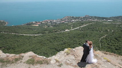 bride and groom on a cliff against blue sky