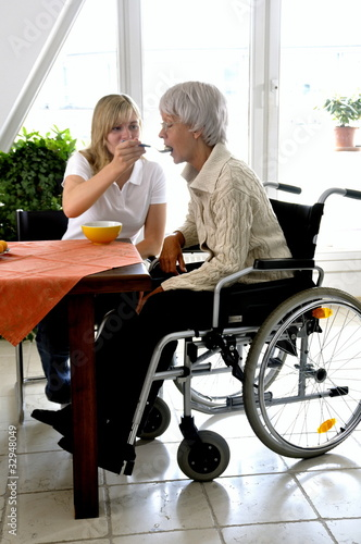 Carer feeding Disabled Woman