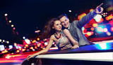 Fototapety Elegant couple traveling a limousine at night