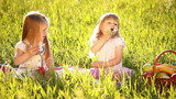 Two sisters blow bubbles in the meadow.