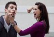 Enraged young woman about to punch her boyfriend