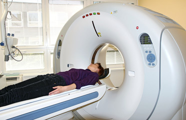 young girl and CT machine in hospital
