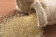 Raw white quinoa grains in jute sack on wood
