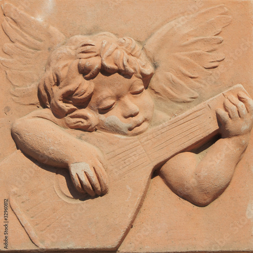 angel playing guitar in terracotta from tuscan Impruneta