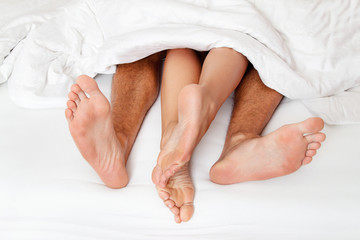 Feet of one couple in bed.