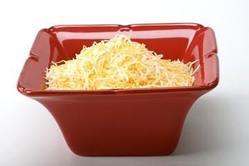 Shredded monterey jack and cheddar cheese in a red ceramic dish
