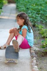 kleines Mädchen verletzt mit Skateboard