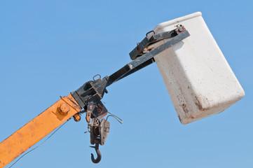 Top part of a heavy crane against a blue sky.