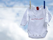 Little babygro on a clothesline in front of blue sky
