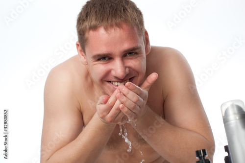 young man washing his face