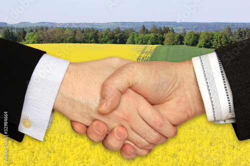 Businessmen shaking hands in front of the the Rape Field