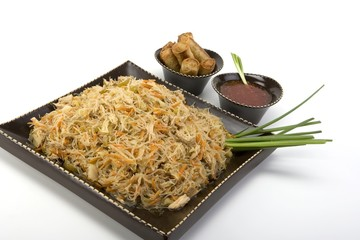 Pancit on a ceramic dish with egg rolls and sweet and sour sauce