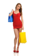 Young Woman wearing a red dress and carrying shopping bags