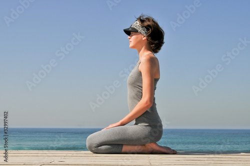 Young girl making exercises on the beach