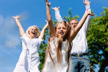 Familie im Freien springt hoch