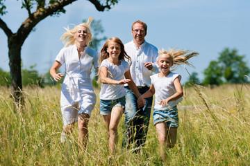 Familie läuft in der Wiese
