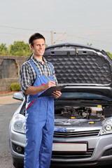 Mechanic with a clipboard standing next to a car with open hood