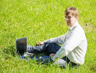 man  on meadow with laptop