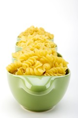 Assorted raw pasta noodles in green ceramic dish