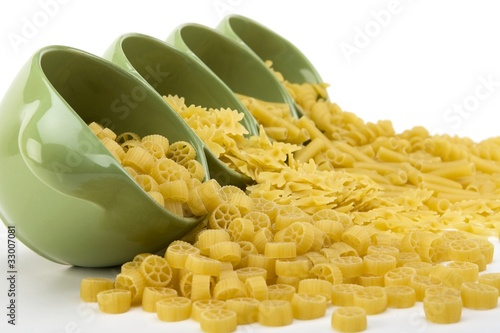 Assorted raw pasta noodles spilling from a green ceramic dish