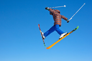 flight of young skier on blu sky background