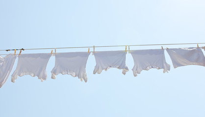 White t-shirt hanging to dry on a clothes-line