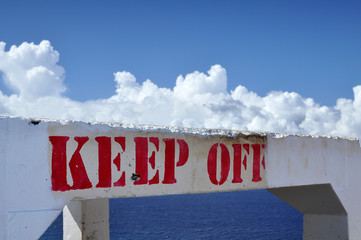 keep off sign, with sky and ocean behind