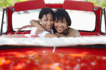 beautiful twin sisters hugging in cabriolet car