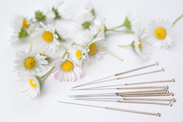 Akupunkturnadeln und Blüten