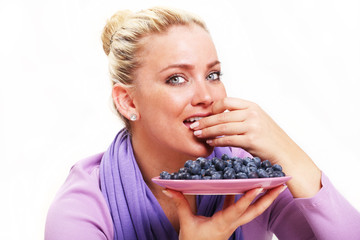 Beautiful Young Woman Eating Blueberries