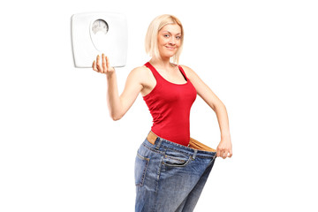 Portrait of a weight loss female holding a weight scale