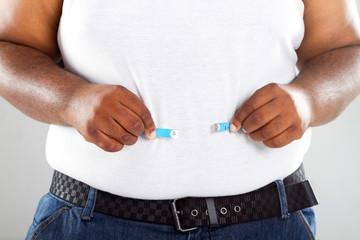 overweight african american man measuring waist