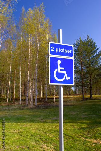 Disabled parking sign on green park