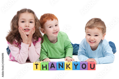 Three happy children with thankyou kids letter blocks