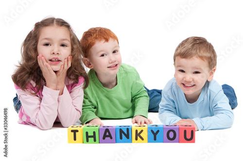 Three happy children with thankyou kids letter blocks