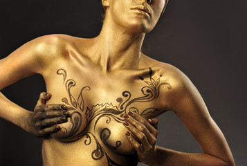 Portrait of young sexy woman in golden paint