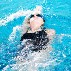 Swimmer in swim meet doing backstroke