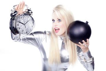 Blonde Frau mit Wecker und Bombe blickt hoch, Zeitbombe