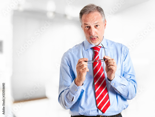 Mature businessman speaking, holding glasses in his hands
